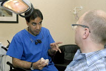 25-07-2008 - A young dentist treating a patient in his practice in Redditch © Timm Sonnenschein