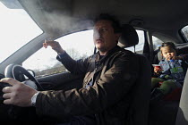 28-03-2010 - Smoker driving his car with a child on the back seat. Doctors demand a review of anti-smoking laws to consider a ban on smoking in all cars to protect the young from second-hand smoke © Timm Sonnenschein