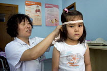 26-07-2011 - A girl having a general health check at the hospital in order for her to attend a local nursery school in Shanghai. China © Timm Sonnenschein