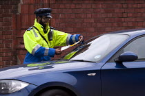 25-10-2012 - A civil enforcement officer placing a ticket on the windscreen of a wrongly parked car otside the Birmingham Courts © Timm Sonnenschein
