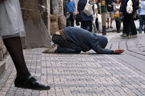 04-06-2012 - A beggar in the streets of Prague as tourists walk by. © Timm Sonnenschein