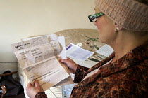05-20-2013 - Maggie looking at a discretionary housing payment from Birmingham City Council regarding her council flat in Moseley, Birmingham. She is required to pay bedroom tax for one room, which she cant pay, t... © Timm Sonnenschein