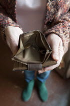 05-20-2013 - Maggie showing her almost empty purse, in her council flat in Moseley, Birmingham. She is required to pay bedroom tax for one room, which she cant pay, the discretionary payment will not help in the l... © Timm Sonnenschein