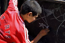 30-10-2005 - A young Palestinian boy draws stars on chunks of metal that have been left after the construction of the security wall which separates people in the Abu Dis area of East Jerusalem. Israel, 2005 © Steven Langdon