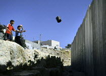 30-10-2005 - Palestinian children throw rubbish at the Israeli security wall near their homes in the Abu Dis area of East Jerusalem. The West Bank, 2005 © Steven Langdon