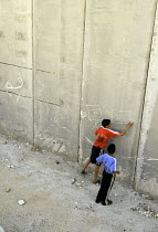 30-10-2005 - Two Palestinian boys draw Israeli and Palestinian flags with chalk near their homes which are next to the Israeli security wall in the Abu Dis area of East Jerusalem. The West Bank, 2005 © Steven Langdon