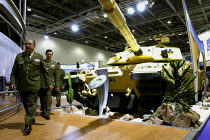 09-09-2003 - A trio of Army officers march past an Alvis Vickers Challenger tank which has been specially adapted for use in desert conditions. Defence Systems and Equipment International Exhibition, Excel, Dockla... © Paul Mattsson