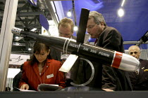 09-09-2003 - Representatives of Diehl Munitions Systems looking at their corporate paperwork. On display is one of their precision guided mortar rounds. Defence Systems and Equipment International Exhibition, Exce... © Paul Mattsson
