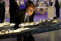 09-09-2003 - Man in a suit looking at model warships and aircraft carrier. Defence Systems and Equipment International Exhibition, Excel, Docklands © Paul Mattsson