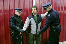 10-09-2003 - An anti arms trade protester is stopped and searched by Metropolitan Police officers under the draconian Terrorism Act 2000 while protesting outside the Defence Systems and Equipment International Exh... © Paul Mattsson