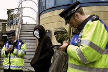 10-09-2003 - Anti arms trade protesters are stopped and questioned by Metropolitan Police officers under the draconian Terrorism Act 2000 while protesting outside the Defence Systems and Equipment International Ex... © Paul Mattsson