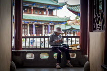 10-09-2015 - An elderly woman embroidering, Cuihu Park, Kunming, Yunnan Province, China. © Connor Matheson