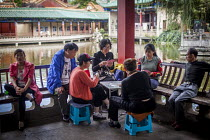 10-09-2015 - Family and friends gambling and playing games of cards Cuihu Park, Kunming, Yunnan Province, China. © Connor Matheson
