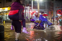 22-09-2015 - Man carrying a woman piggyback through flooded streets after heavy rain. Lijiang, Yunnan Province, China. © Connor Matheson