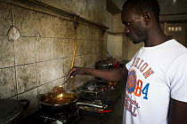 14-07-2015 - Refugee from Africa cooking food in the communal kitchen. Marsa Open Centre, Malta. © Connor Matheson