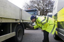 06-03-2015 - Trucks pulled over as part of the regular roadside checks by DVSA staff to ensure that HGVs are safe to drive on British roads. A vehicle inspector with many years experience inspects a vehicle. © Stefano Cagnoni