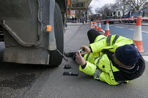 06-03-2015 - Trucks pulled over as part of the regular roadside checks by DVSA staff to ensure that HGVs are safe to drive on British roads. A vehicle inspector with many years experience inspects worn tyres on an... © Stefano Cagnoni