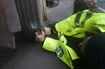 06-03-2015 - Trucks pulled over as part of the regular roadside checks by DVSA staff to ensure that HGVs are safe to drive on British roads. A vehicle inspector with many years experience shines a light on damaged... © Stefano Cagnoni