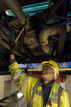 06-03-2015 - A vehicle inspector with many years experience inspects a bus engine from a garage inspection pit © Stefano Cagnoni