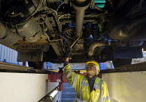 06-03-2015 - A vehicle inspector with many years experience inspects a bus engine from a garage inspection pit. © Stefano Cagnoni