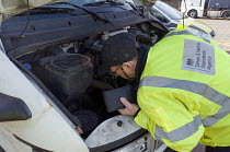 10-03-2015 - Trucks pulled over as part of the regular roadside checks by DVSA staff to ensure that HGVs are safe to drive on British roads. A vehicle inspector at a permanent check site off the M25 inspecting the... © Stefano Cagnoni