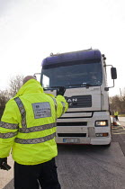 10-03-2015 - Trucks pulled over as part of the regular roadside checks by DVSA staff to ensure that HGVs are safe to drive on British roads. A vehicle inspector at a permanent check site off the M25 halts an HGV,... © Stefano Cagnoni