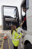 10-03-2015 - Trucks pulled over as part of the regular roadside checks by DVSA staff to ensure that HGVs are safe to drive on British roads. A female vehicle inspector at a permanent check site off the M25 prepare... © Stefano Cagnoni