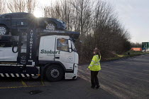 10-03-2015 - Trucks pulled over as part of the regular roadside checks by DVSA staff to ensure that HGVs are safe to drive on British roads. A female vehicle inspector at a permanent check site off the M25 directi... © Stefano Cagnoni