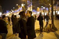 11-12-2015 - Couple kiss on the Champs Elysee infront of a muslim woman begging, Paris © Jess Hurd