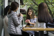 09-12-2015 - Hanoi, Vietnam, Young women play cards at a cafe © David Bacon