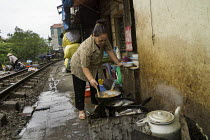 09-12-2015 - Homes next to the railway tracks, Hanoi, Vietnam. Cook preparing food for her small restaurant © David Bacon
