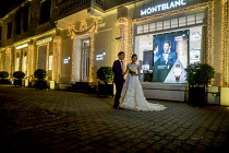 05-01-2016 - Hanoi, Vietnam, bride and groom having their picture taken at night by Hotel Metropole, a custom for women about to get married © David Bacon