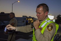 23-06-2016 - Las Vegas, Nevada, Police sobriety checkpoint, Vegas Valley Drive, detaining a driver for suspected alcohol or drug impairment. A police officer holds a Duquenois-Levine field test kit that shows the... © Jim West