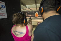 30-06-2016 - Las Vegas, Nevada - A woman fires her handgun at the Discount Firearms + Ammo indoor shooting range. © Jim West