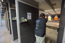 30-06-2016 - Las Vegas, Nevada - A man fires his handgun at the Discount Firearms + Ammo indoor shooting range. © Jim West