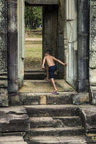 21-12-2015 - Cambodia, Khmer child playing in the ruins at the Elephant Platform, near Angkor Wat. People live in and around the temple sites and children are permitted to play on the ruins © David Bacon