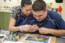 30-06-2016 - Las Vegas, Nevada, Instructor helping, Fine Art Program for disabled by the nonprofit Opportunity Village. Artists are paid a commission on the sale of their artwork © Jim West