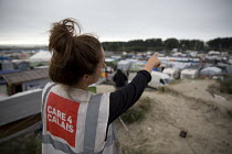 07-09-2016 - Care 4 Calais charity volunteer surveys the Calais Jungle camp, France. © Jess Hurd