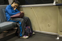 10-09-2016 - California, an exhausted passenger asleep on the Bay Area Rapid Transit train between San Francisco and Oakland © David Bacon