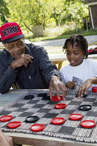 24-09-2016 - Detroit, Michigan, Elderly man and a young boy playing draughts at a block party © Jim West