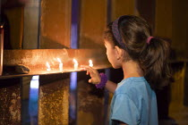 08-10-2016 - Nogales, Arizona, Religious activists hold a candlelight vigil at the USA Mexican border fence. A woman on the USA side lights a candle through the fence for a Mexican girl. The interfaith religious c... © Jim West