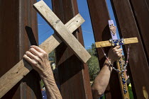 08-10-2016 - Nogales, Sonora Mexico, Women in the USA hold crosses through the border fence. Religious activists hold rallies on both sides of the USA-Mexican border fence. Protests at the increasing militarizatio... © Jim West