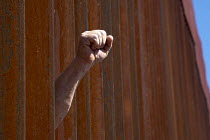 08-10-2016 - Nogales, Sonora Mexico, fist is raised as Religious activists hold rallies at both sides of the USA Mexican border fence. Protests at the increasing militarization of the border, the separation of imm... © Jim West