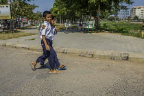 25-12-2015 - Battambang, Cambodia. Two boys walk together with their arms around each others shoulders © David Bacon