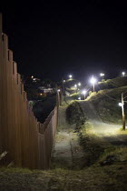 08-10-2016 - Nogales, Arizona, USA and Mexican border fence lit up at night by the U.S. Border Patrol. Mexico is on the left side of the fence © Jim West