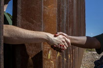 08-10-2016 - Nogales, Sonora Mexico, Hands reach out from the USA side of the border fence to shake the hand of a person on the Mexican side. Religious activists hold rallies at both sides of the USA Mexican borde... © Jim West