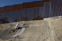 10-08-2016 - Nogales, Sonora Mexico, graffiti artists paints a mural below the U.S.-Mexico border fence. © Jim West