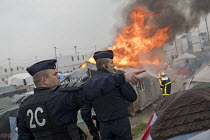 26-10-2016 - CRS as a Firefighter sprays fires during the eviction of refugees from the Jungle camp, Calais, France © Jess Hurd