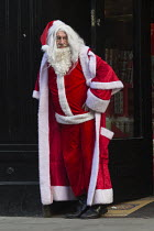 16-12-2016 - Santa Claus doorman calling shoppers to a temporary Christmas shop, Swindon Shopping precinct, Wiltshire © John Harris