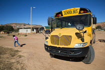 11-10-2016 - Thoreau, New Mexico - A Navajo girl runs home after being dropped off by a school bus from St. Bonaventure Indian School, a Catholic school on the Navajo Nation © Jim West